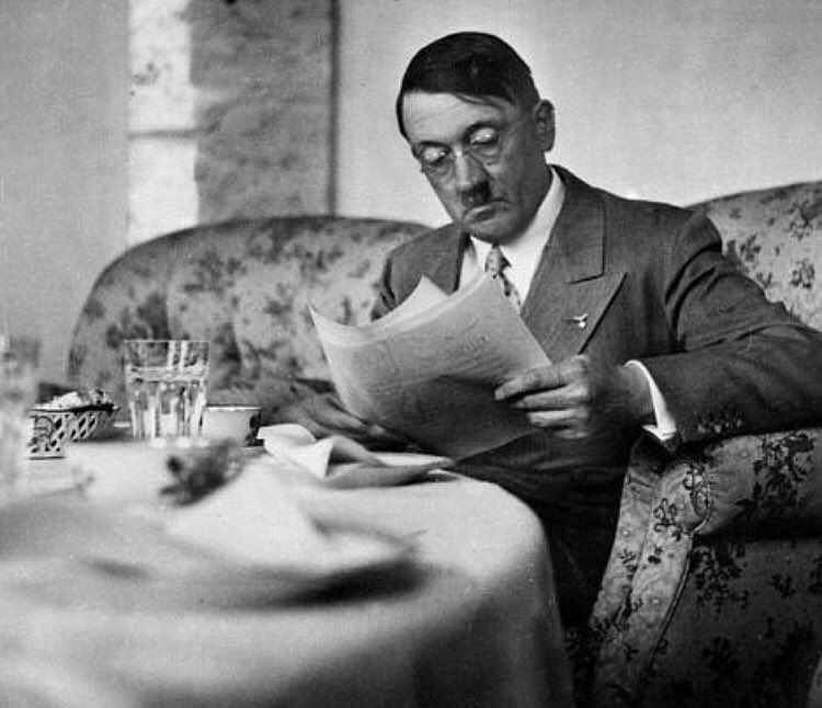 Adolf Hitler wearing reading glasses at the breakfast table at his home Berghof in Berchtesgaden, Germany