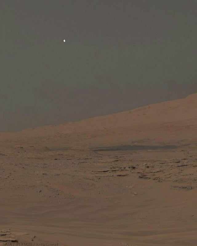 Afternoon on Mars. Moon Phobos peeking over the northern limb of Mount Sharp